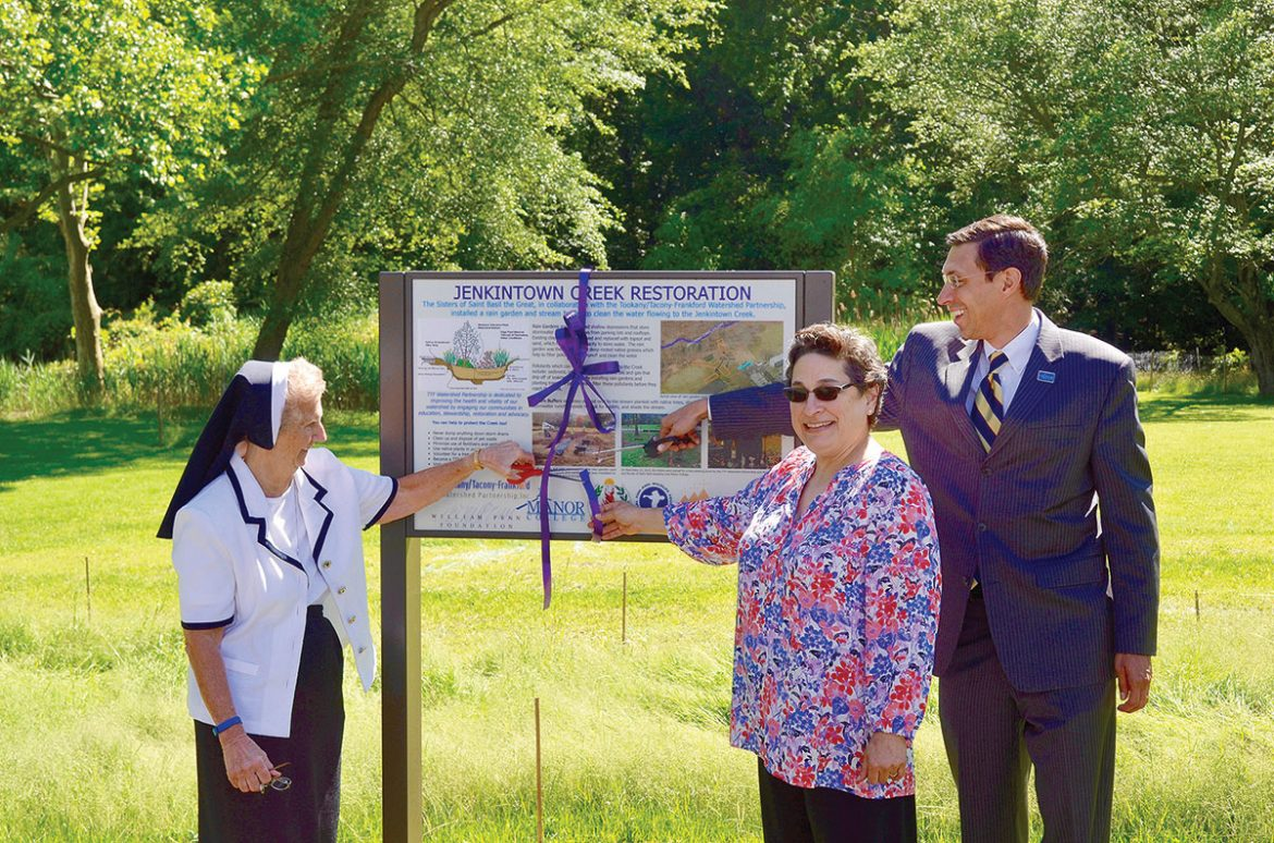 Cutting the ribbon to unveil a new rain garden are (from left): Sister Dorothy Ann Busowski, provincial superior, Sisters of St. Basil the Great; Julie Slavet, executive director, Tookany/Tacony-Frankford Watershed Partnership Inc.; and Jonathan Peri, president of Manor College.