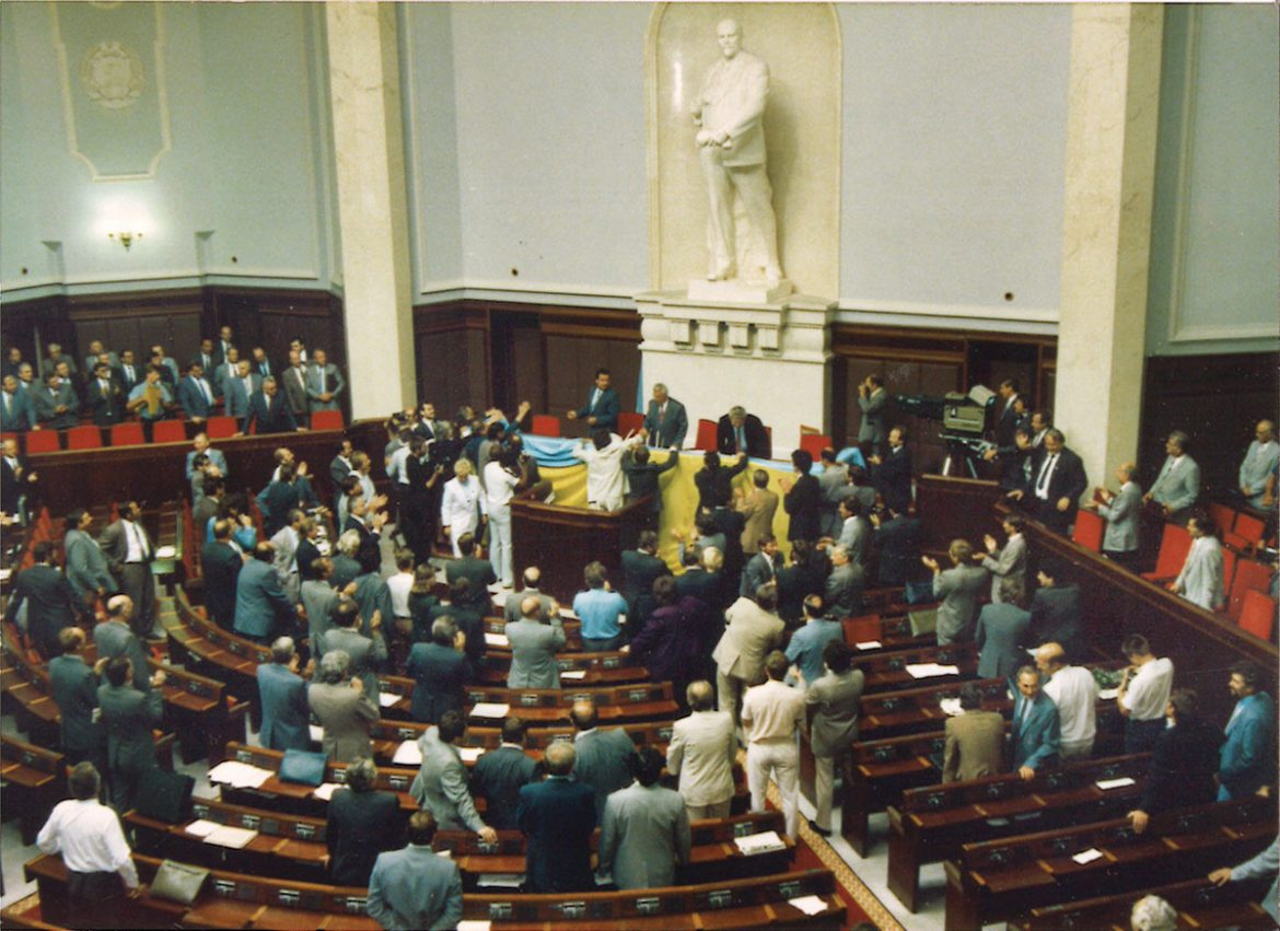 August 24, 1991: After the overwhelming vote for Ukraine's independence, national deputies drape a Ukrainian flag on the Verkhovna Rada chairman's podium. The statue of Lenin that looms over the proceedings would soon be gone.