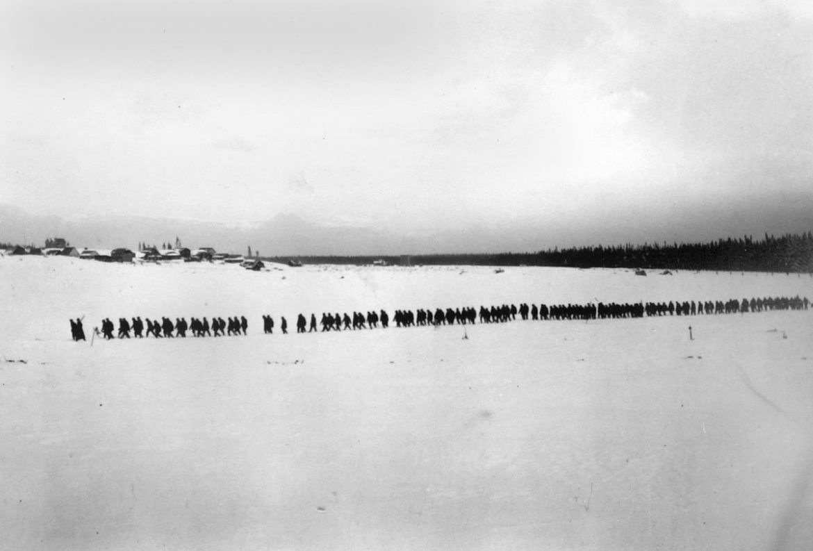 Internees cross Spirit Lake with the internment site in background, circa 1915.