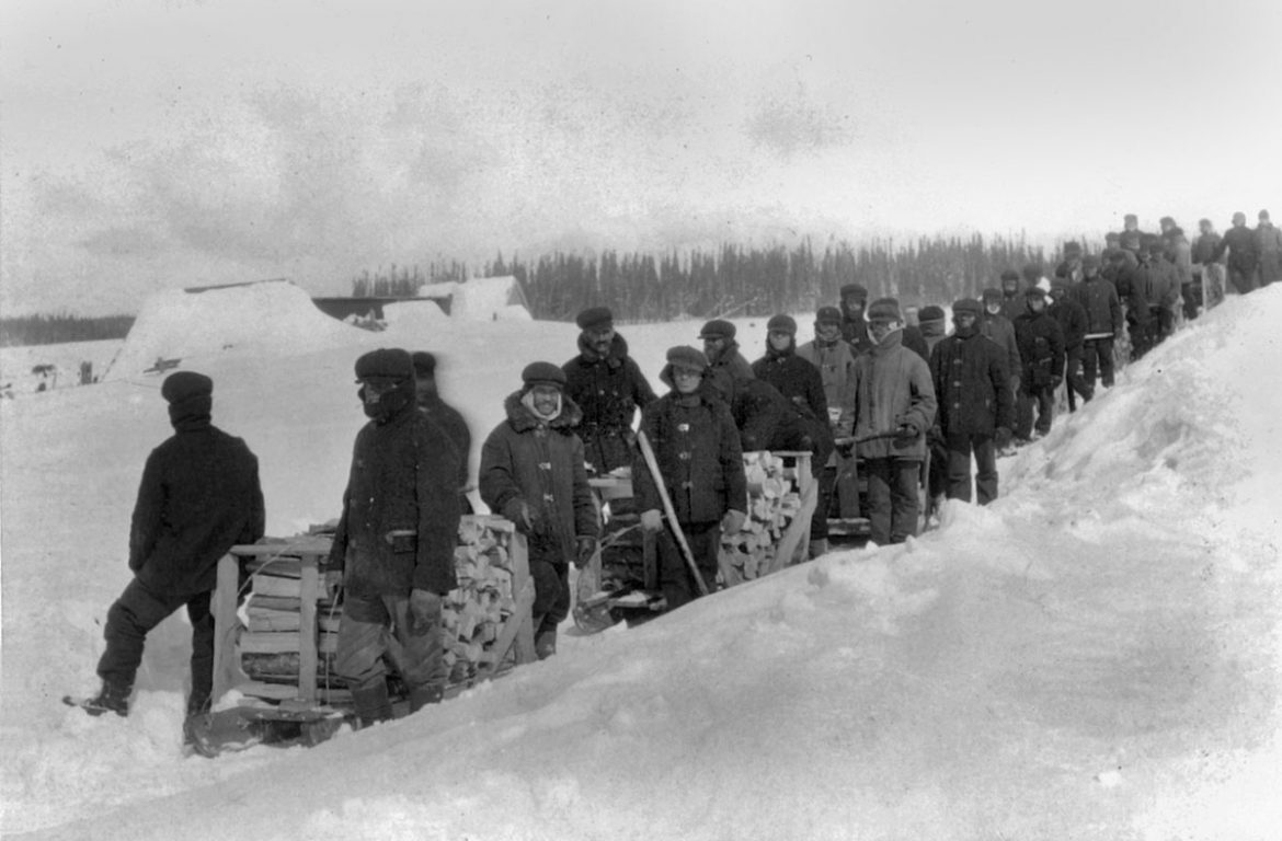 Internees in winter are led back to the compound after being forced to cut wood, Spirit Lake circa 1915.