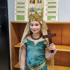 Ruslana Orysia Makar, dressed as St. Princess Olha, stands before her informative poster about the ruler of Kyivan Rus'.