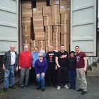 Volunteers load a shipping container with humanitarian aid items destined for various regions of Ukraine.