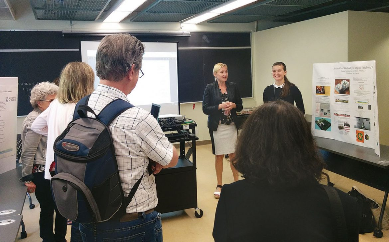 Alla Nedashkivska (center) introduces poster session participant Daria Pоlianska.