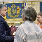 Ukrainian President Petro Poroshenko presents the Hero of Ukraine medal to the parents of Mikhail Zhyzneuski in Kyiv on June 13.