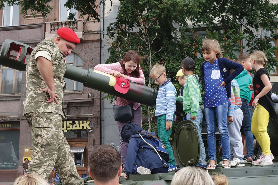 A mother watches her son climb into a tank, while other children await their turn. The tank is on display on the Khreshchatyk as part of an exhibition on how military equipment has developed since the beginning of Russia's war on Ukraine.