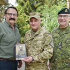"""Lubomyr Luciuk (left) presents a copy of """"A Canadian Hero,"""" about Cpl. Filip Konowal, to Col. Ihor Slisarchuk of Ukraine's armed forces at the International Peacekeeping and Security Center in Lviv Oblast on July 15, as Lt.-Gen. Paul Wynnyk of the Canadian Army (right) looks on."""