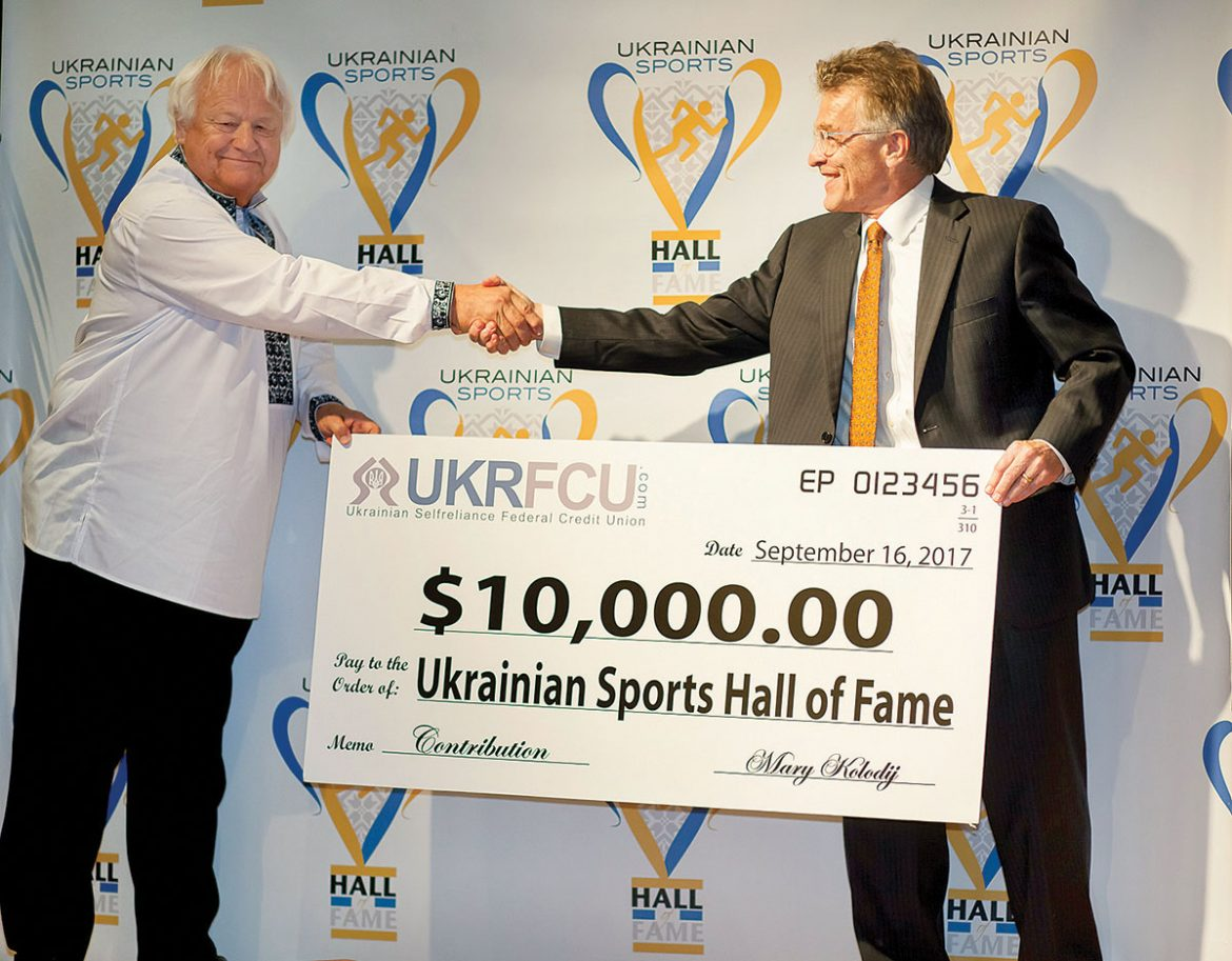 Roman Petryk (right), chairman of Ukrainian Selfreliance Federal Credit Union, presents a donation for the Ukrainian Sports Hall of Fame to Myron Bytz.