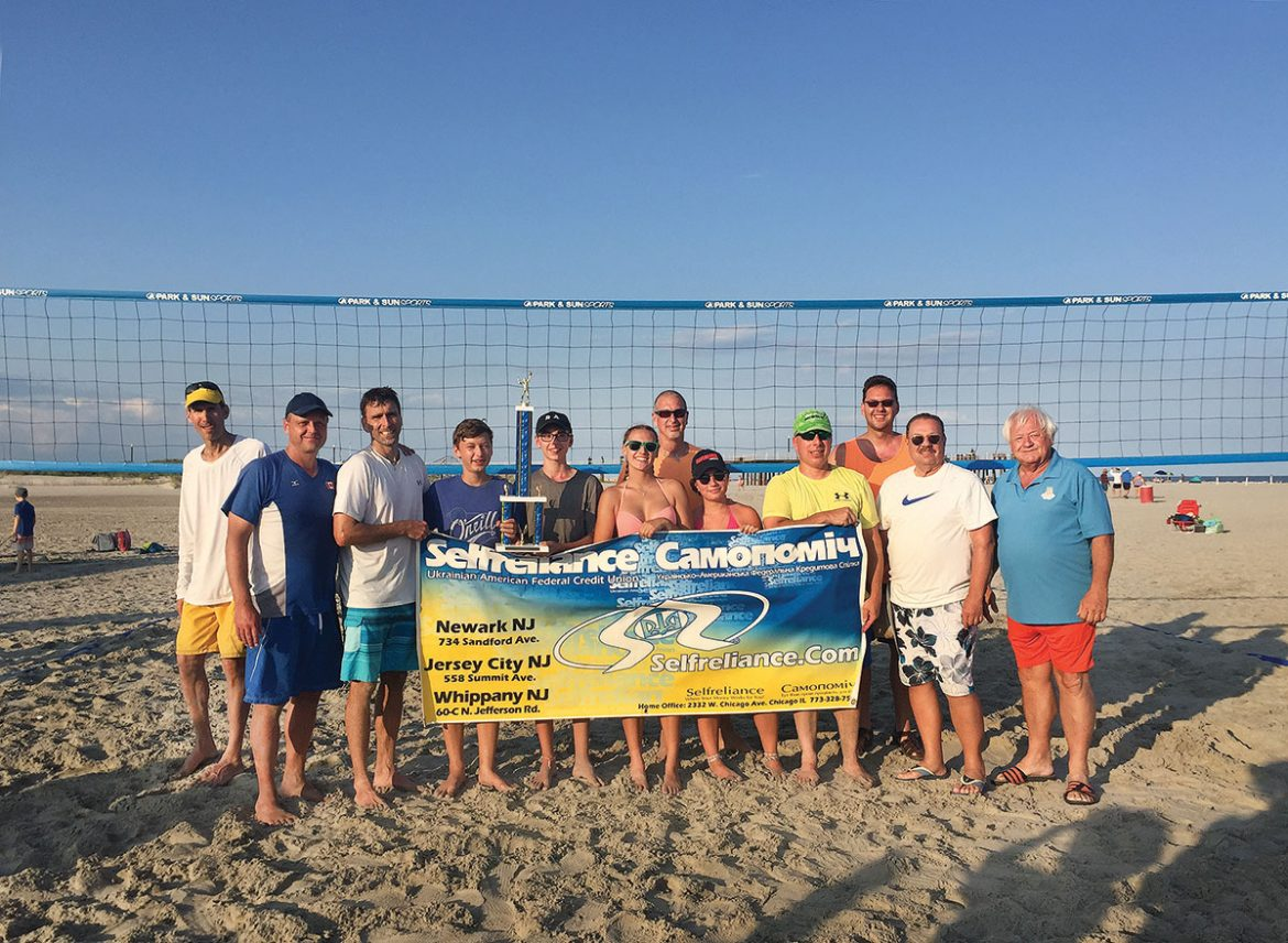 """The 2017 USCAK beach volleyball champions, """"Babushkas,"""" (second through fifth from left) and 2017 finalists """"ROMMA"""" (far left, and fourth through seventh from right) with USCAK tournament organizers Myron Bytz (far right) and Roman Bulawski (third from right), and Michael Koziupa (second from right) of Selfreliance Ukrainian American Federal Credit Union, a tournament sponsor."""