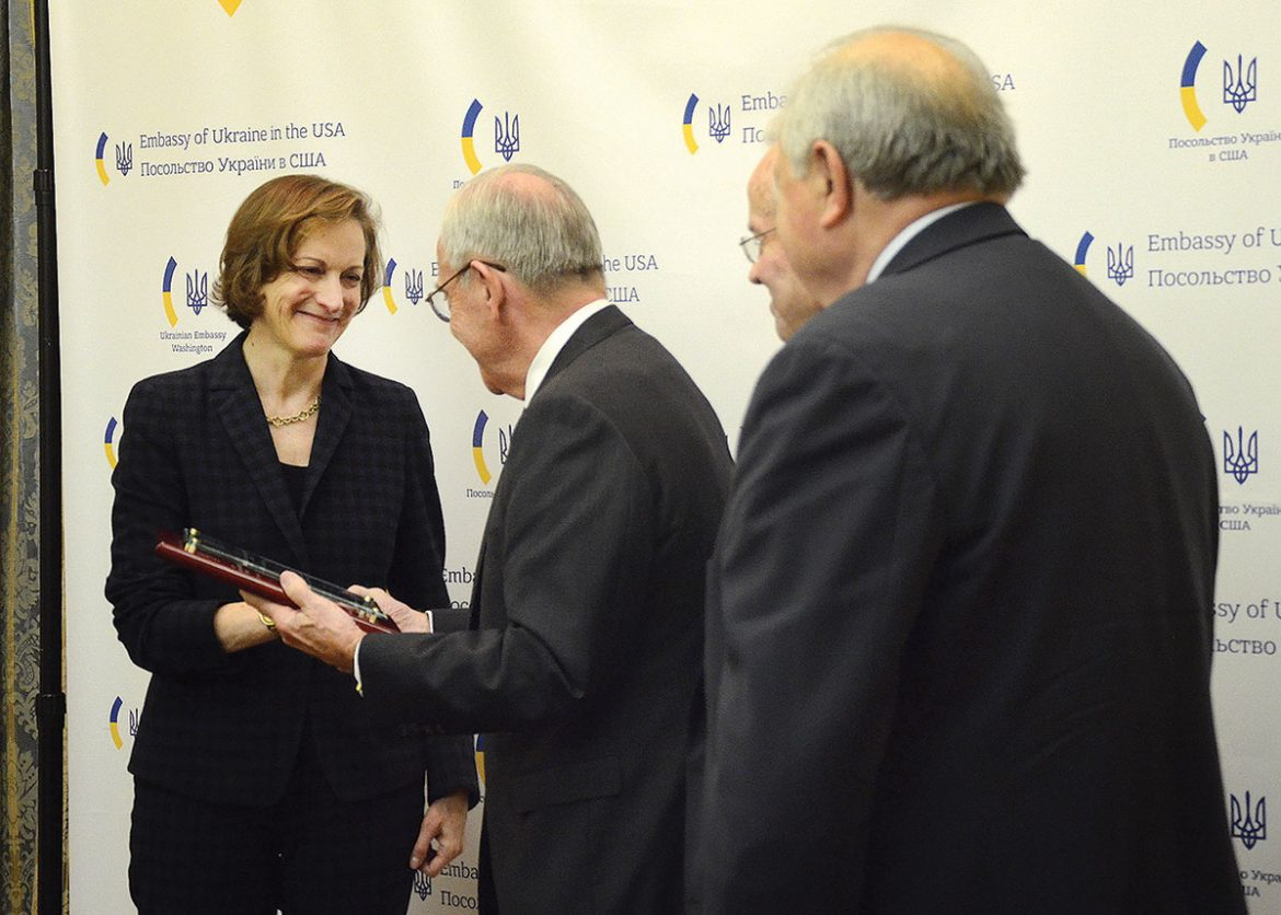 "The director of the Omelan and Tatiana Antonovych Foundation, Dr. Ihor Voyevidka, presents Anne Applebaum with the 2017 Antonovych Award for her ""coverage of Ukraine in international media and the pursuit of historical truth."" Standing behind him are two other members of the board, Andrew Lewycky and Dr. Roman Szporluk."