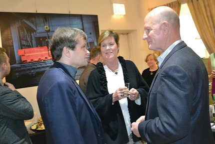 """Congressman Mike Quigley and Chicago Blackhawks player Reggie Kerr chat with fellow attendees at the opening of the """"Outtakes"""" exhibit."""