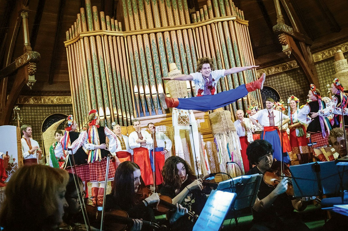 """Michael Szafran leaps into action during the Boston performance of """"Zaporozhets za Dunayem"""" as members of the Syzokryli Dance Ensemble and combined choruses look on."""