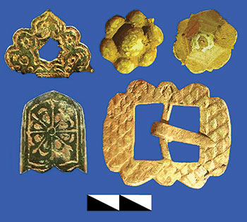 Bronze decorative appliqués and clasp from belts of Kozak officers, unearthed at the site of early 18th-century barracks in 2014. (Photo by Yurii Sytyi.)