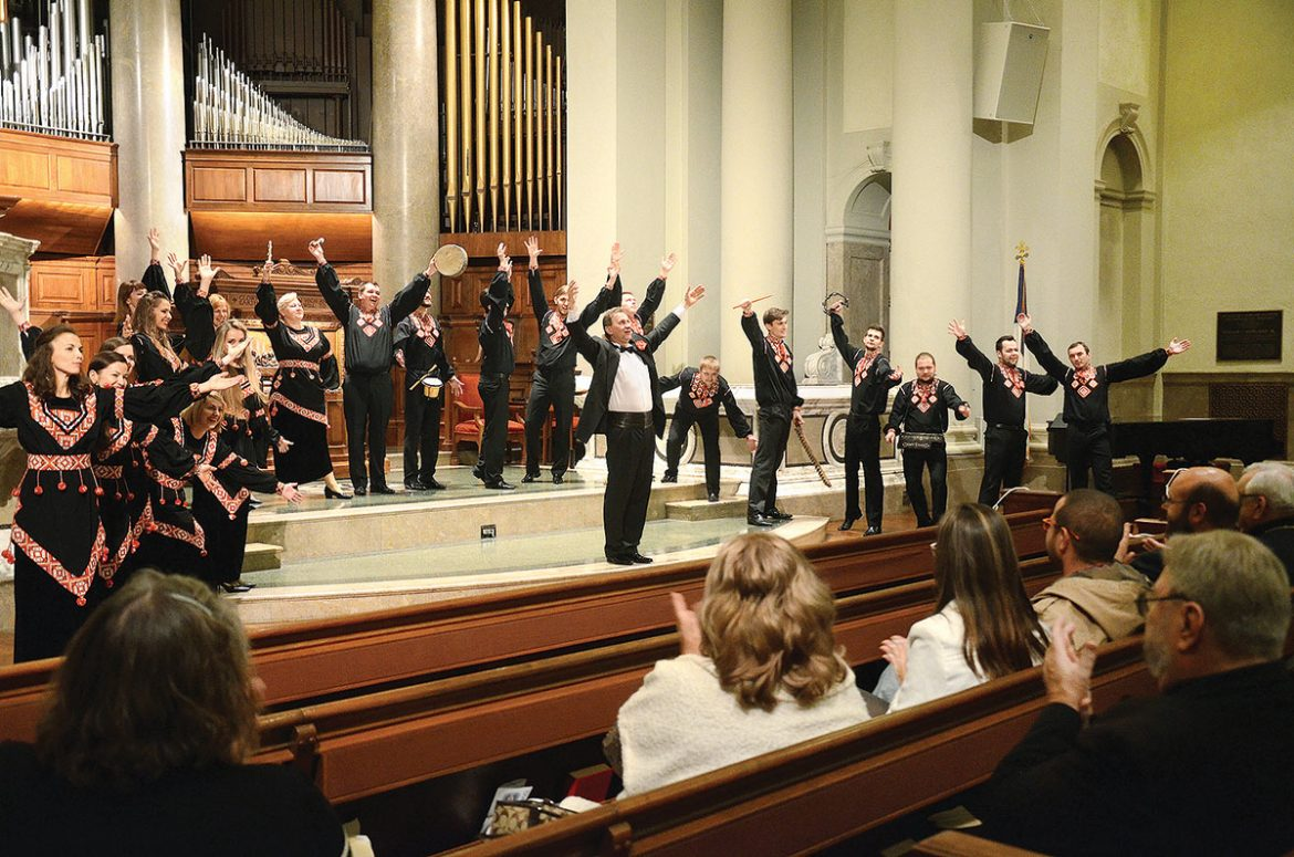 """Kyiv Chamber Choir conductor Mykola Hobdych joins his choristers in responding to the audience's ovation at the conclusion of their Ukrainian sacred and folk music concert at the National City Christian Church in Washington on November 6. The concert was part of the choir's """"Sounds of Ukraine"""" tour of the U.S."""