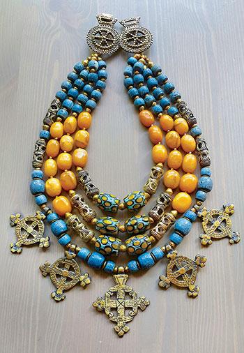 A necklace by Slava Salyuk, features yellow honey jade, Ghanaian Krobo beads, old Venetian trade beads, Ashanti brass beads, Coptic crosses, and brass Hutsul fibulas.