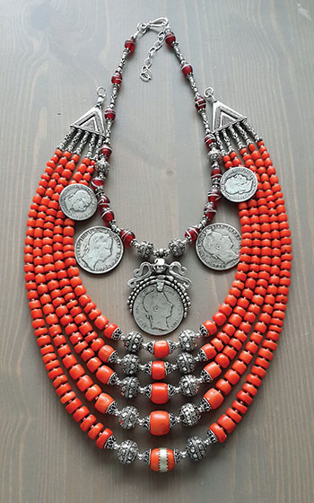 """Another necklace by Slava Salyuk incorporates antique red coral, sterling silver beads, vintage red flower Venetian trade beads and antique silver Austrian coins of the late 1800's. The """"dukach"""" features a silver pendant with a Franz Josef coin."""