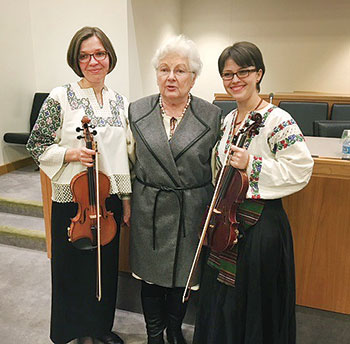 Dr. Martha Bohachevsky Chomiak is flanked by violinists Anastasia Antoniw (left) and Iryna Kit (right).