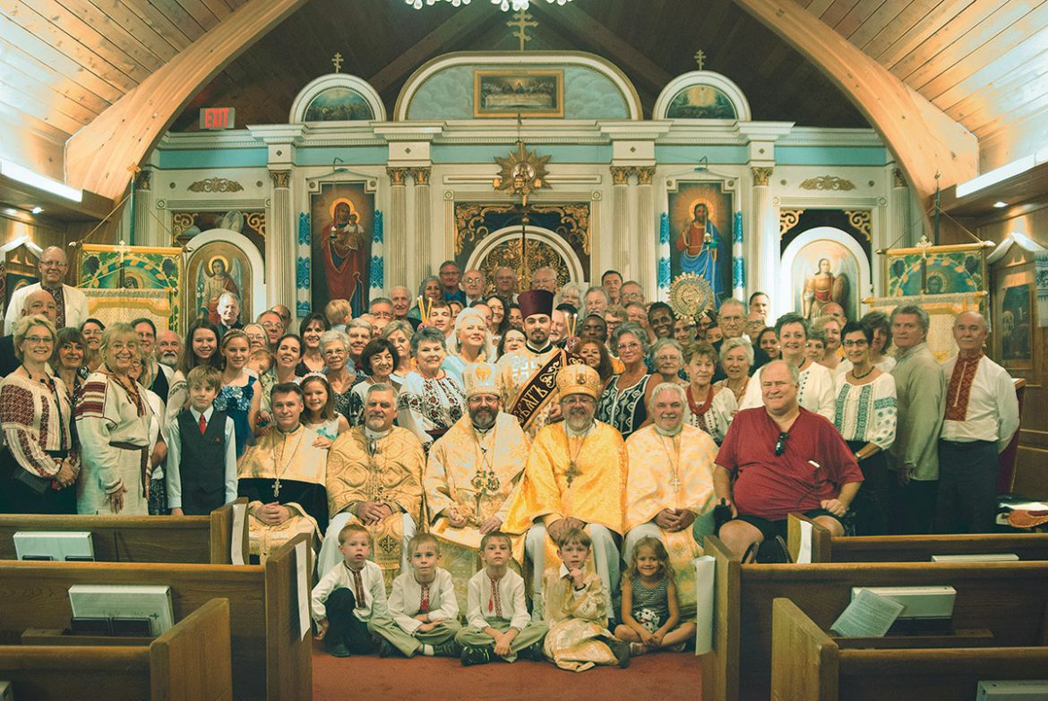 Parishioners and visitors crowd around Patriarch Sviatoslav to fix a moment in history at little St. Michael Ukrainian Greco-Catholic Church in Tucson, Ariz.