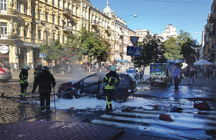In this photograph taken by Olena Prytula before she realized her partner, Pavel Sheremet, was in the explosion on July 20, 2016, firefighters douse the vehicle in a Kyiv street.