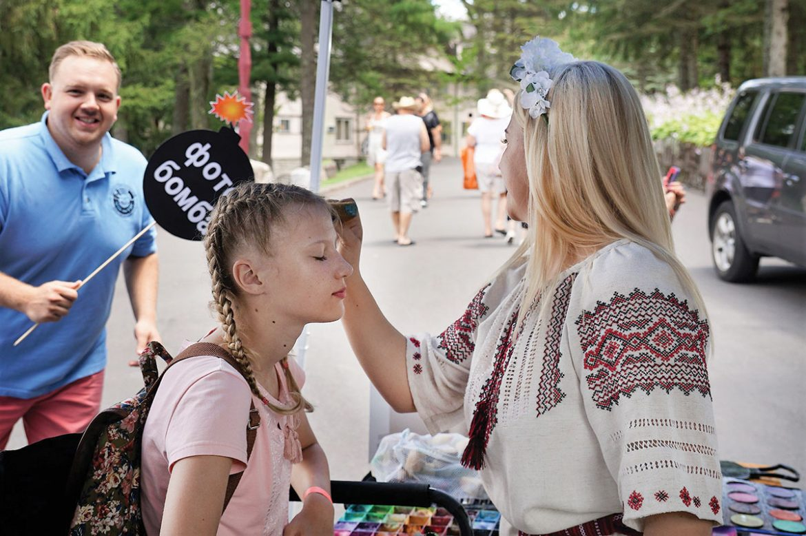 Athena Zhe (right) applies face paint to a girl, while Ukrainian National Association Secretary Yuriy Symczyk adds a well-timed photo bomb.