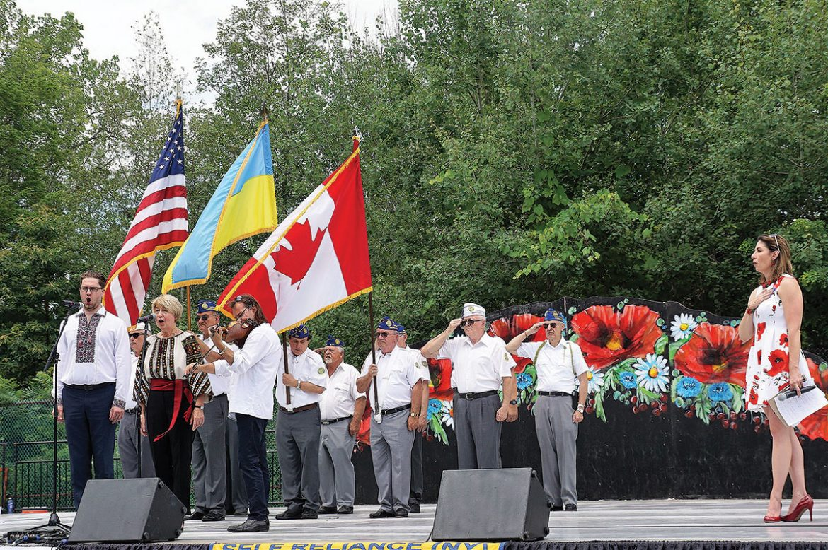 During the opening ceremonies, (from left) Andrij Gavdanovich, Swiatoslava Kaczaraj and Vasyl Popadiuk perform the national anthems of the United States, Canada and Ukraine with Ukrainian American Veterans serving as a color guard. On the right is MC Lydia Kulbida.