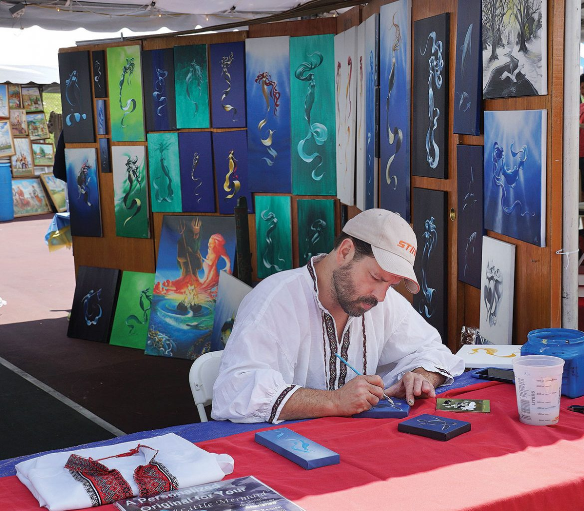 An artist produces pieces of art in front of visitors' eyes at the vendors' court.