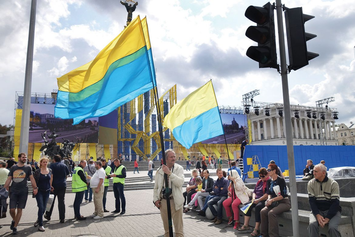 A man holding a Ukrainian flag stands on Kyiv's Maidan. Prior to Independence Day, Ukraine celebrates National Flag Day, August 23.