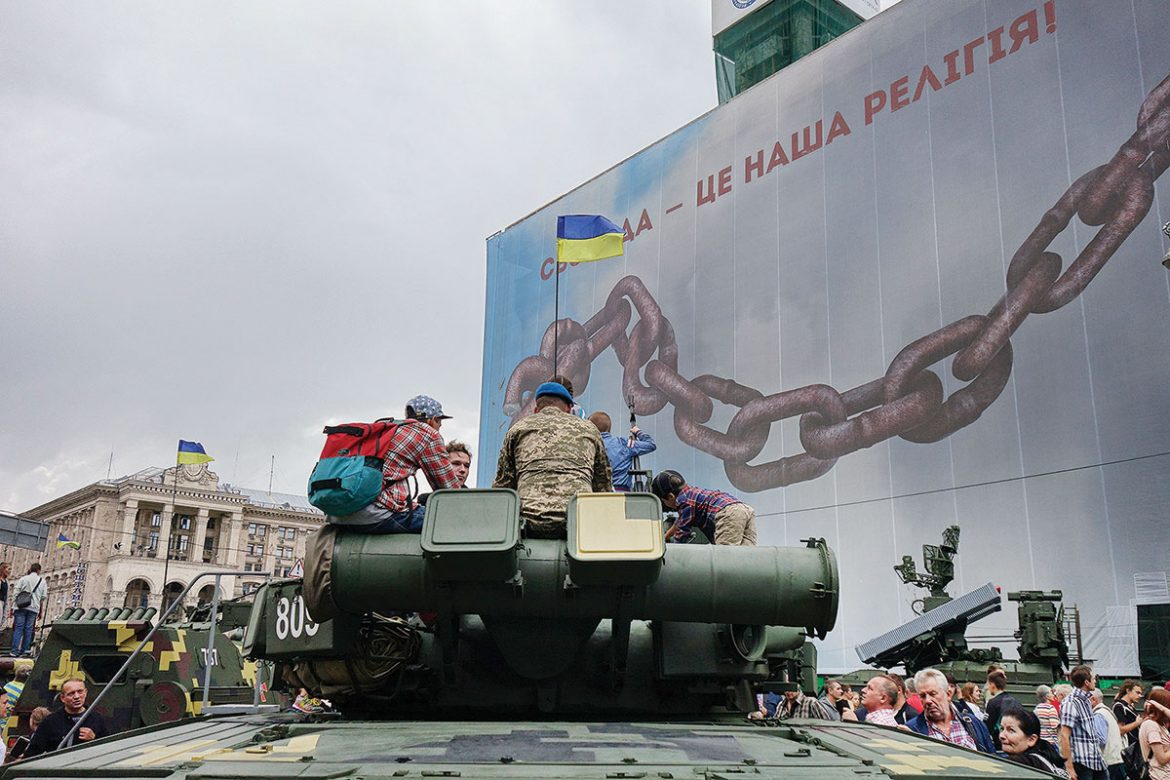 """A Ukrainian soldier and a group of young people sit and talk atop a tank on display on Kyiv's Khreshchatyk on August 23. Behind them, the former Trade Union building is covered with a banner that reads """"Freedom is Our Religion."""""""