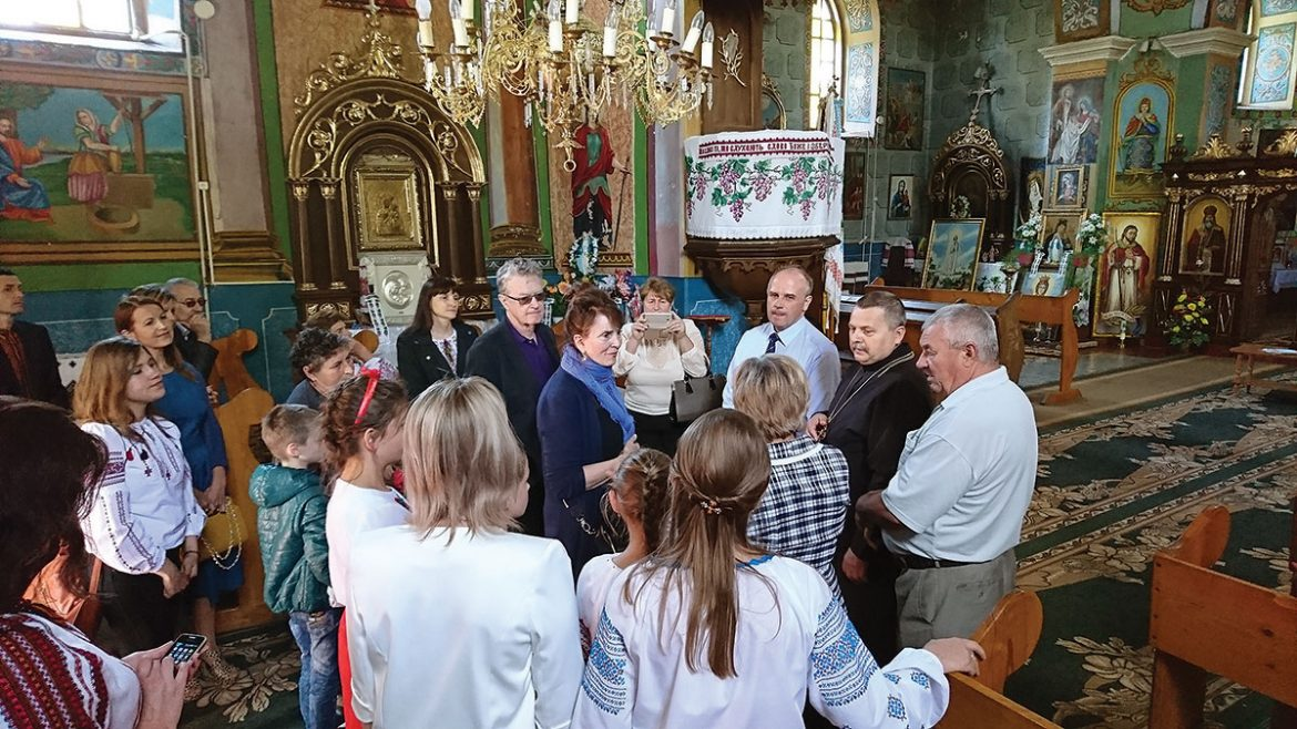 Holly Palance (center) inside the village's Ukrainian Greek-Catholic church with her husband, Robert Wallace (left), the priest, and the mayor standing next to him on September 15.