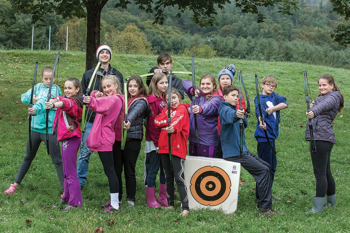 Enthusiastic scouts, with their counselors, show off their archery skills.