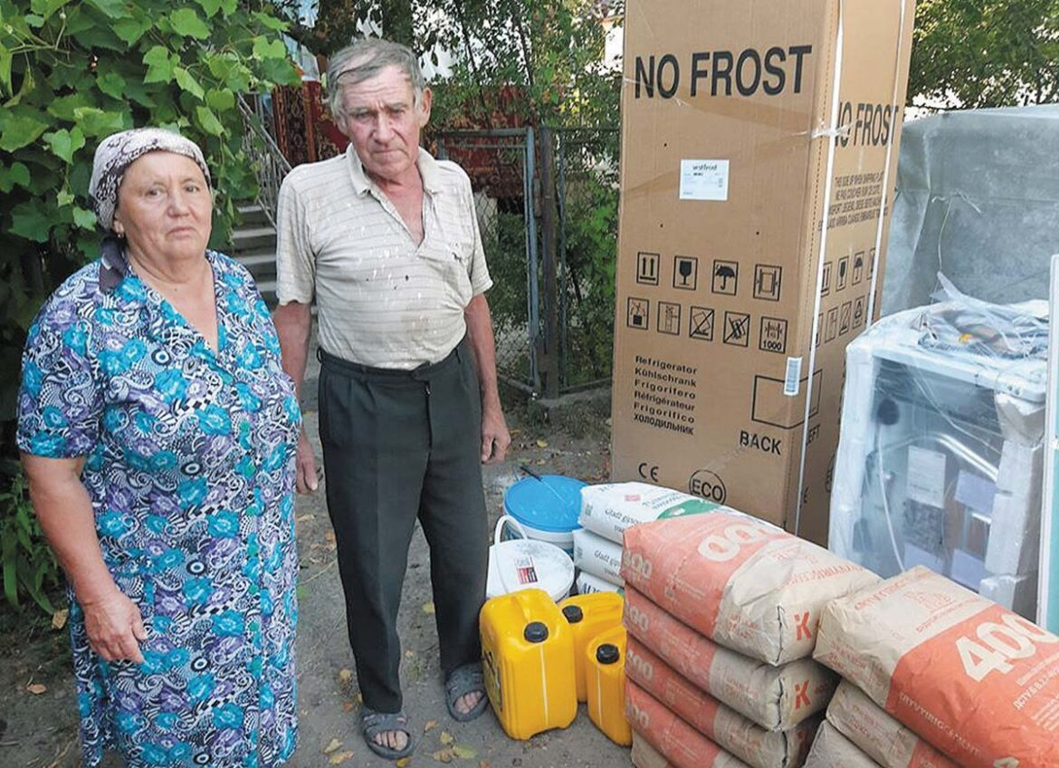 Woman and man receiving aid in Ivano-Frankivsk from the Ukrainian Catholic Church after heavy rains and flooding